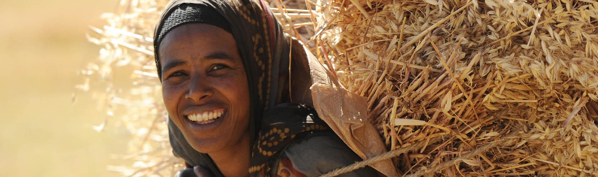 Frau trägt Getreide