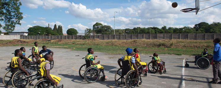Children in wheelchairs play basket ball.