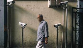 September 23, 2019, Shanghai, China - An elderly man ewalks past four newly installed security cameras in a laneway in Xuhui District. China has around 200 million surveillance cameras. (Dave Tacon/Polaris) ///