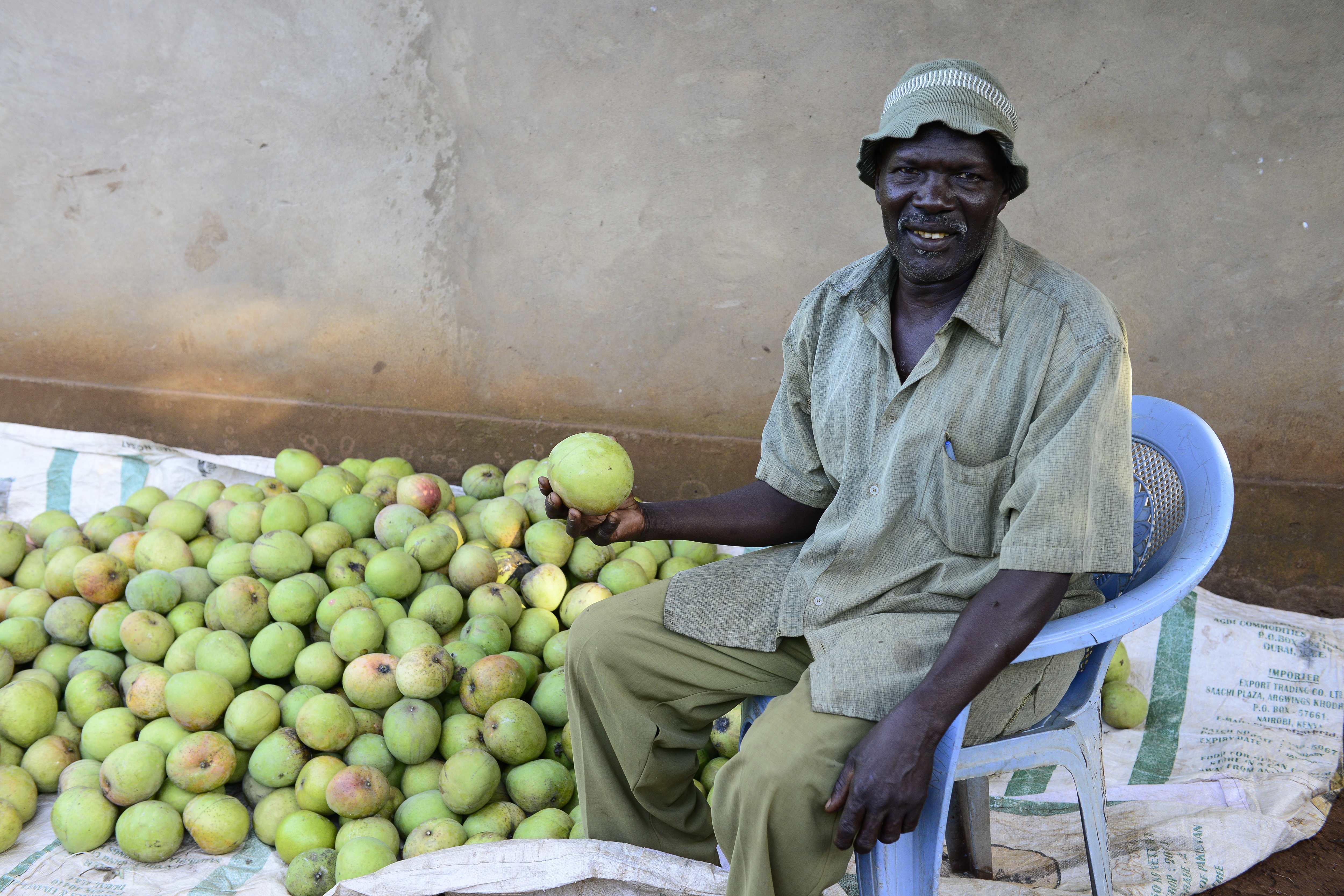 Herr John Mwenduna erzielt ein zusätzliches Einkommen mit dem Verkauf von Mangos