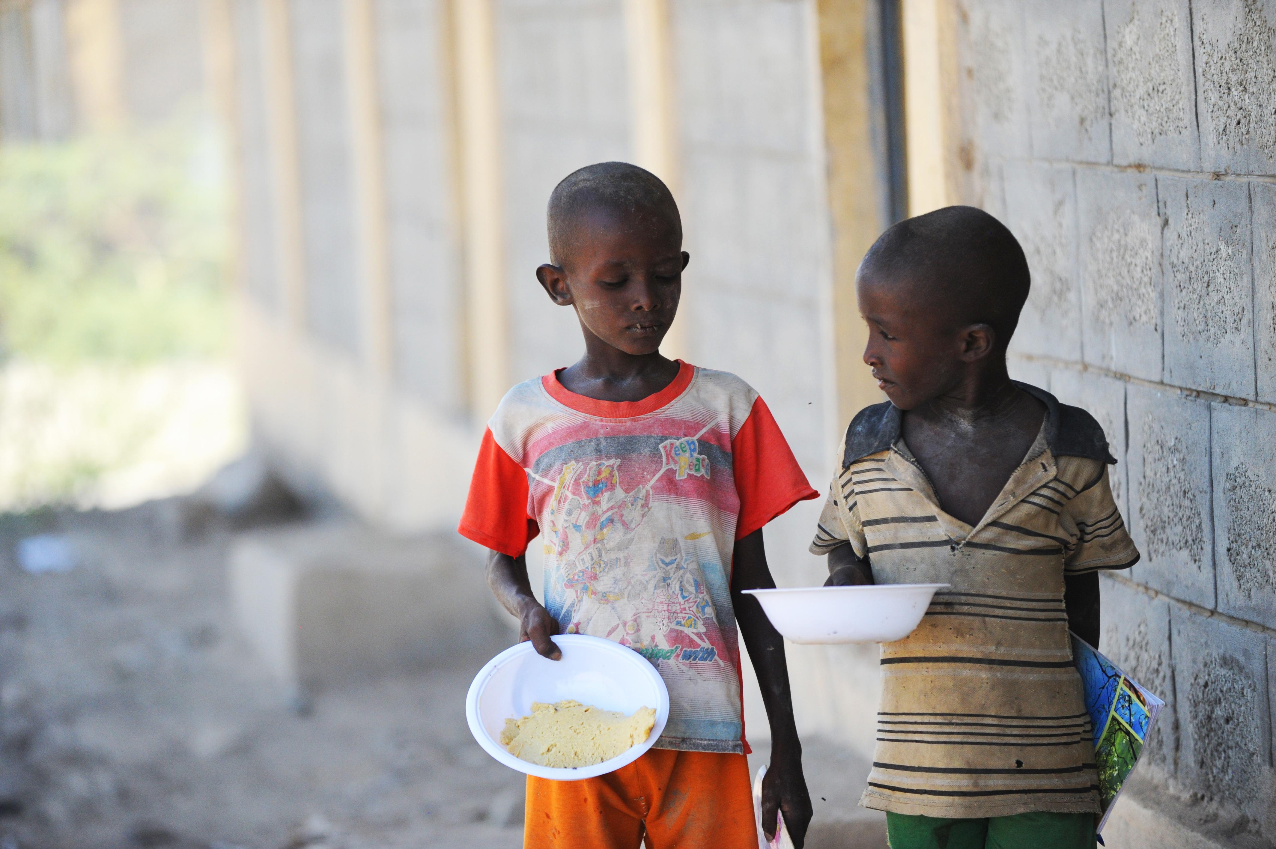 Zwei Kinder mit Tellern auf denen Famex ist. Famex wird während der Dürre als Nahrung besonders für Kinder verteilt um Unternährung zu vermeiden.